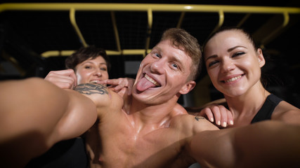 Two girl and one man making selfie photo in gym