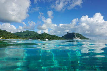 Coastal landscape of Huahine island near the village of Fare, seen from calm water surface of the lagoon, Pacific ocean, French Polynesia