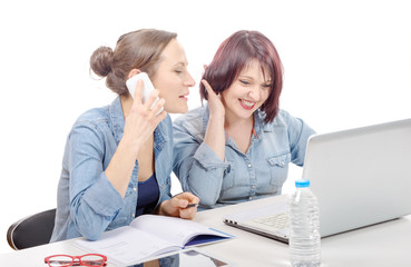 Smiling businesswomen using cell phone in office