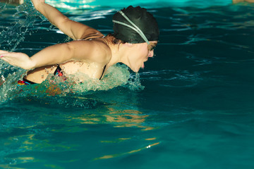 Woman athlete swimming butterfly stroke in pool.