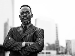African businessman portrait in the city with crossed arms monochrome