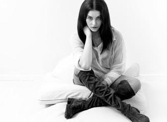 Pretty girl portrait sitting on cushions black and white