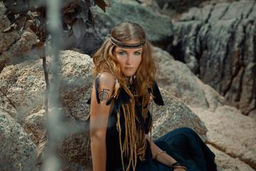 young beautiful boho woman on the rocks