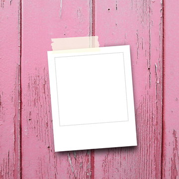 Close-up of one blank instant polaroid photo frame with adhesive tape on pink weathered wooden boards background