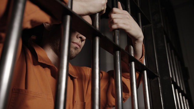 Caucasian Prisoner behind bars in Jail - Criminal Justice system