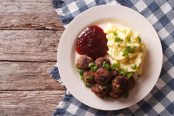 fried meatballs, lingonberry sauce with potato garnish. Horizontal top view