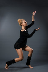 Modern classical dance theme: beautiful girl dancing sensual dance in a studio on a gray background