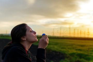 Portrait of beautiful woman blowing bubbles in park
