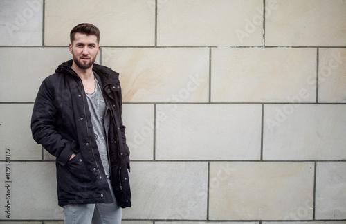 attraktiver mann vor einer mauer stockfotos und lizenzfreie bilder auf bild. Black Bedroom Furniture Sets. Home Design Ideas