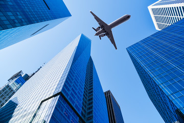 Wall Mural - airplane over office buildings