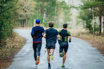 Fotomurales - runners three men running down road in woods. feet in a spray of dirt