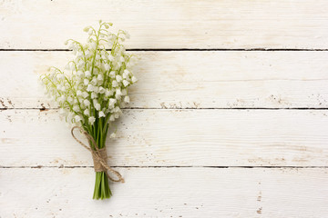 lily of the valley bouquet of white flowers tied with string on a white background barn boards. with space for posting information