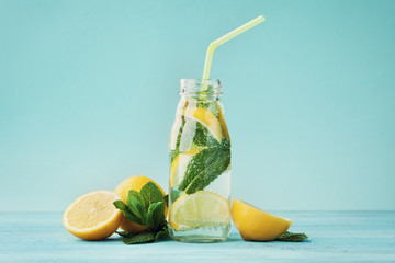 Lemonade drink of soda water, lemon and mint leaves in jar on turquoise background