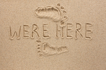 Word WERE HERE written on the sand