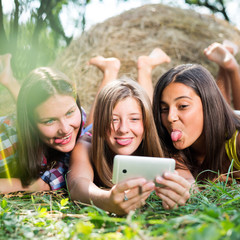 Three happy young girlfriends doing selfie by phone