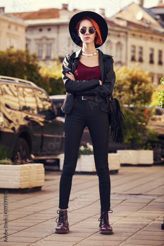 9bc1fc8d51c Model wearing wide-brimmed hat and stylish leather clothes. Girl looking at  camera. Female fashion. City lifestyle