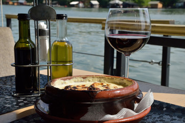 Delicious dish and glass of wine by the river
