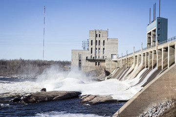 horizontal image of a large water dam with water gushing from the turbines with great speed in the summer time with room for text.