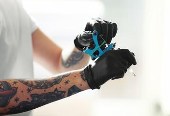 Man's hands holding tattoo machine on blurred background