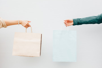 Female and male hands holding shopping bags
