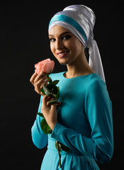 Muslim woman in blue dress with rose flower