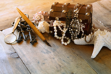 white pearls necklace in treasure chest next to seashells