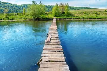 Photo sur Aluminium Pont Old wooden bridge through the river