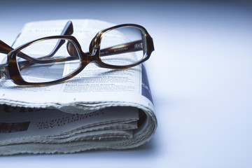 Glasses on newspaper, blue tone