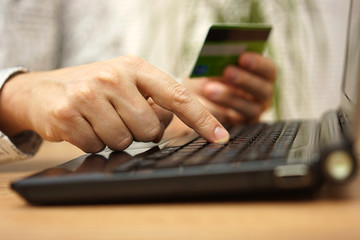 closeup of young person  entering credit card number on laptop c