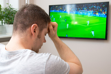 Sad man watching football match on television at home.