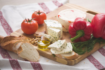 Variety of home made cheese and paprica and herbs, olive oil, olives and bread on a wooden board. brined curd white cheese with vegetables on the table