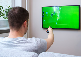 Man watching football match on television at home.