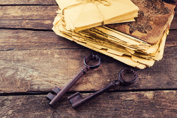 Composition of old books, keys and other things on wooden background, close up