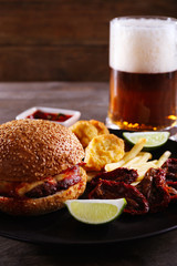 Big tasty hamburger with snacks and glass mug of light beer on wooden table