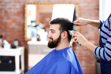 Professional hairdresser cutting hair with hair clipper