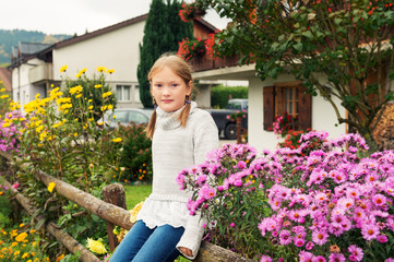 Outdoor portrait of a cute little girl of 8 years old, sitting on a fence, wearing warm grey pullover