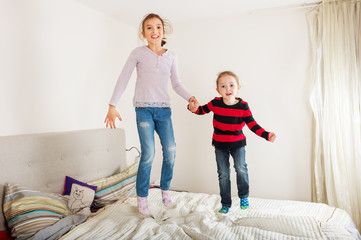 Two sisters jumping on the bed
