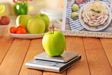 Apple and digital kitchen scales on wooden table