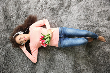 Young woman with tulips listening to music on the floor