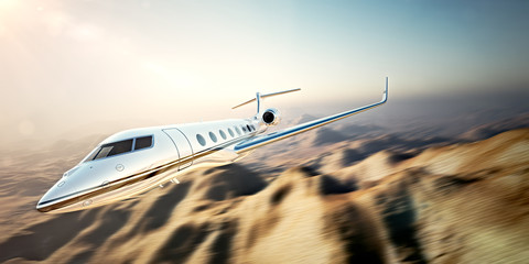 Image of white modern and luxury generic design private jet flying in blue sky at sunset.Uninhabited desert mountains background.Business travel picture.Horizontal,motion blurred effect.3d rendering