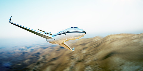 Photo of white modern and luxury generic design private jet flying in blue sky over earth.Uninhabited desert mountains background.Business travel picture.Horizontal,motion blurred effect.3d rendering
