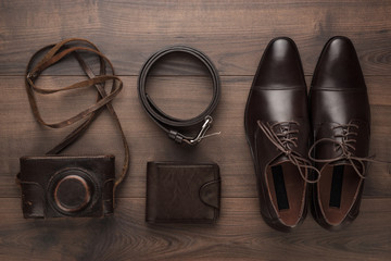 brown shoes, purse, belt, and film camera on wooden table