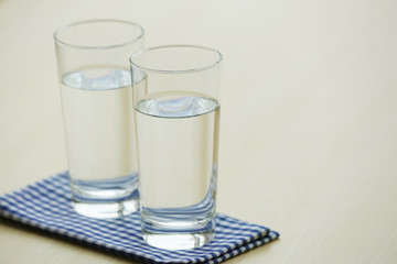 Glasses of pure water on light wooden table