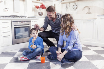 portrait of family relaxing on floor in the kitchen