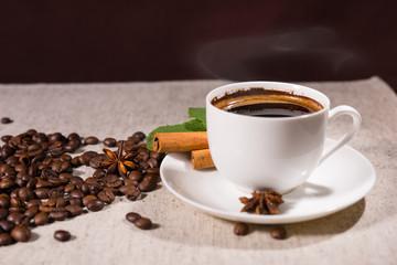 Coffee mug by cinnamon sticks and loose beans