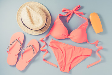 Pink swimsuit with beach accessories on blue background