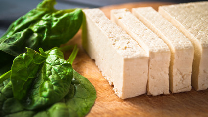 Slices of raw tofu and spinach