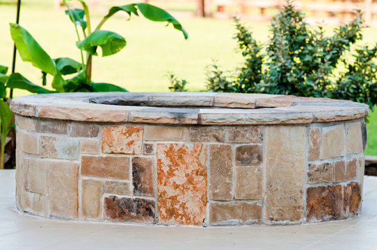 Outdoor flagstone firepit with landscape in background.