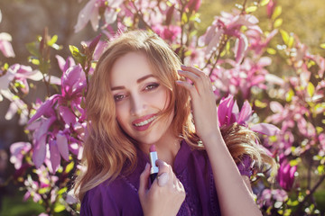Outdoor portrait of a young beautiful  happy smiling lady using lipstick near magnolia tree with flowers. Model looking at camera. Girl wearing stylish clothes. Female spring fashion
