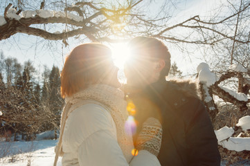 Happy kissing couple on winter park background